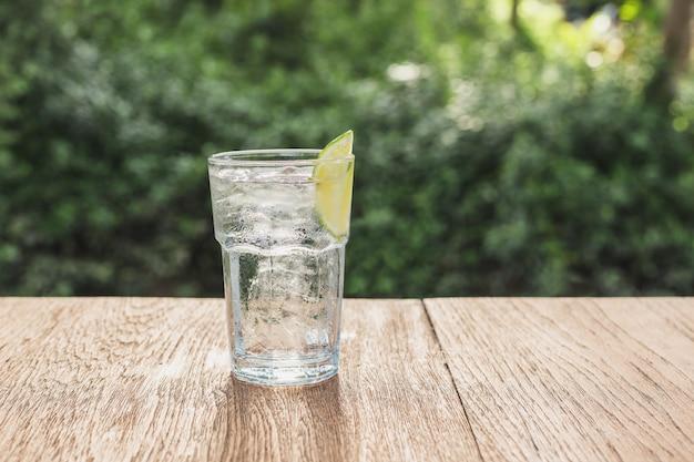 Glas frisches trinkwasser und limettenscheibe auf holztisch.