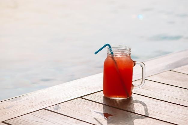 Glas frisches wassermelonen-smoothie-saftgetränk am rand eines swimmingpools - tropisches urlaubskonzept