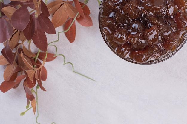 Glas fruchtmarmelade mit blättern auf weißem hintergrund.