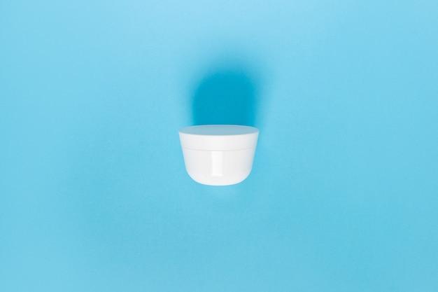 Glas für flüssigkeit, creme, gel, lotion. kosmetikglas auf blau. flach liegen