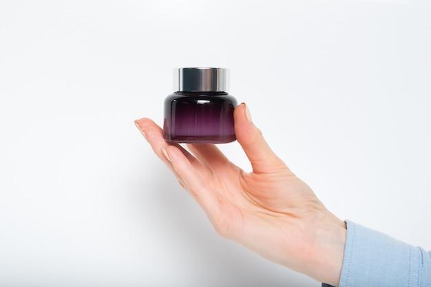 Glas für kosmetik in weiblicher hand,