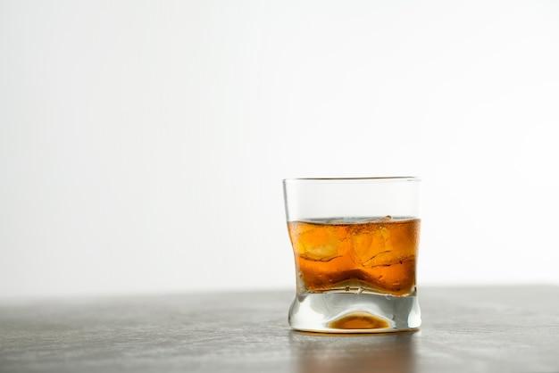 Glas gealterter goldener whisky mit eiswürfeln auf dem tisch. bernsteinfarbenes alkoholisches getränk mit steinen an der bar