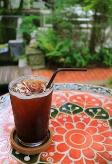 Glas gefrorener kaffee auf einer tabelle im sommer-garten, unscharfer hintergrund