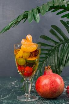 Glas gemischte früchte und granatapfel auf marmortisch