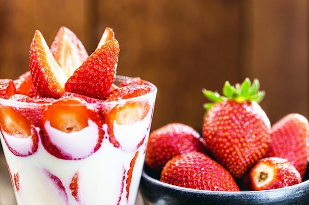 Glas geschnittene erdbeeren mit kondensmilch, typisch brasilianisches dessert