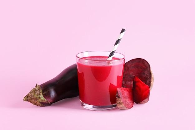 Glas gesunder smoothie mit rüben und auberginen auf farboberfläche