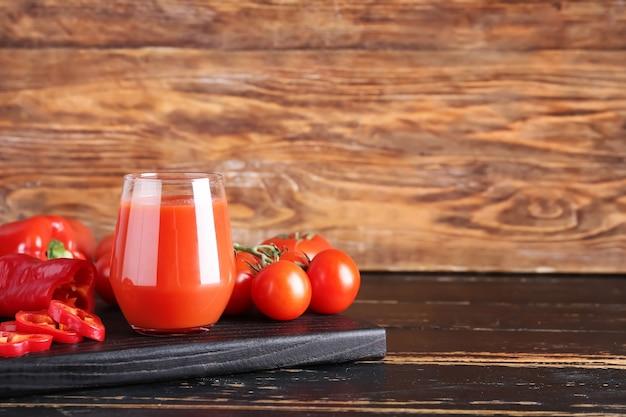 Glas gesunder smoothie mit tomate und paprika auf holzoberfläche