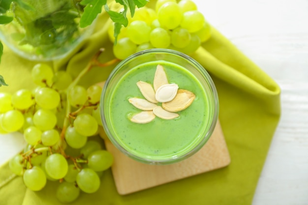 Glas gesunder smoothie mit zutaten auf weißem tisch