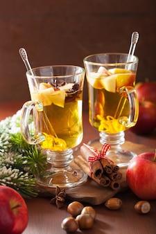 Glas glühapfelwein mit orange und gewürzen, weihnachtsdekoration
