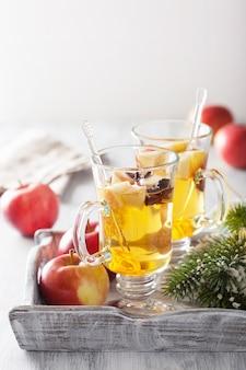Glas glühapfelwein mit orange und gewürzen, wintergetränk