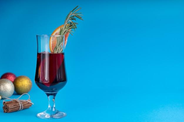 Glas glühwein mit orangenscheibe, zimtbündel und frischem rosmarin mit weihnachtsschmuck