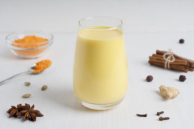 Glas gold oder milch serviert mit einem löffel kurkumapulver, anis und gewürzen auf weißem holztisch
