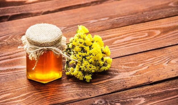 Glas goldenen honigs auf einem alten tisch.