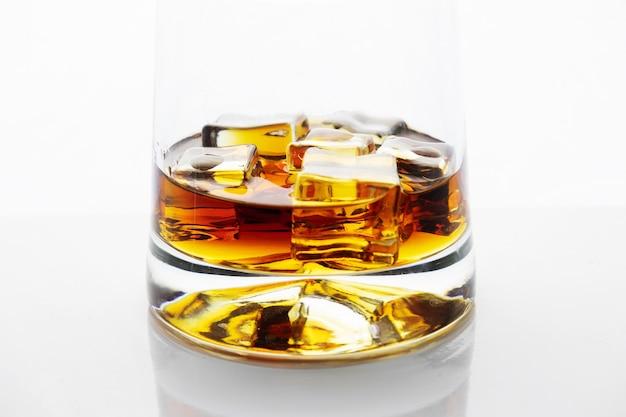 Glas goldener alkohol mit eiswürfeln auf weißer reflektierender oberfläche, whisky oder cognac, nahaufnahme.