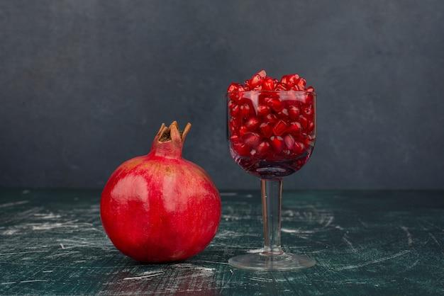 Glas granatapfelkerne und granatapfel auf marmoroberfläche