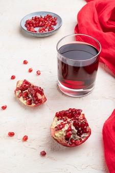 Glas granatapfelsaft auf weißem betonhintergrund mit rotem textil