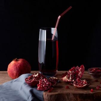 Glas granatapfelsaft mit granatapfelscheiben und granatfrucht auf einem hölzernen brett.