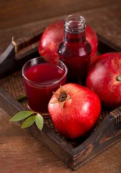 Glas granatapfelsaft und granatapfelfrucht auf holztisch
