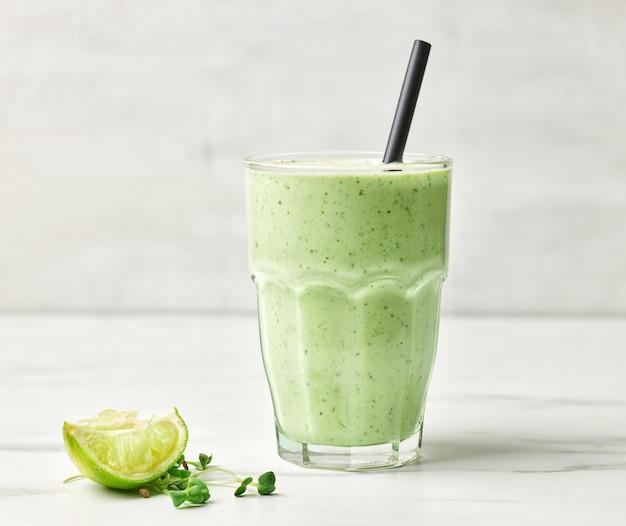 Glas grüner gesunder frühstücks-smoothie auf dem küchentisch