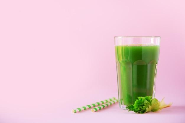 Glas grüner sellerie smoothie auf rosa hintergrund