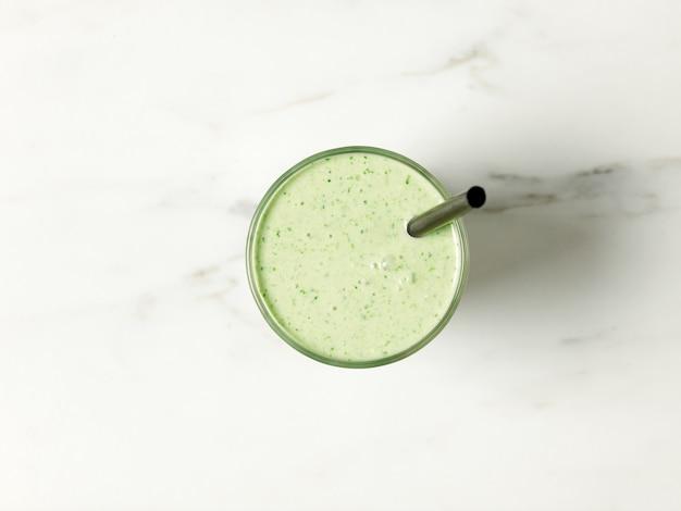 Glas grüner smoothie auf weißem küchentisch, ansicht von oben