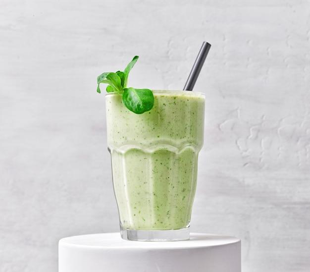 Glas grüner smoothie auf weißem ständer