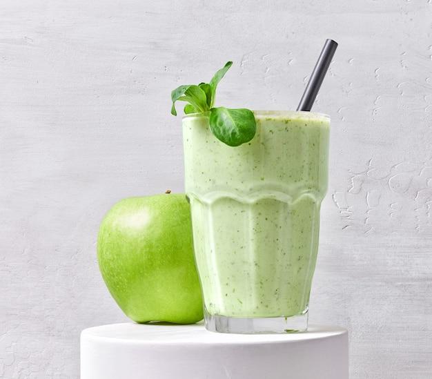 Glas grüner smoothie und apfel auf weißem stand