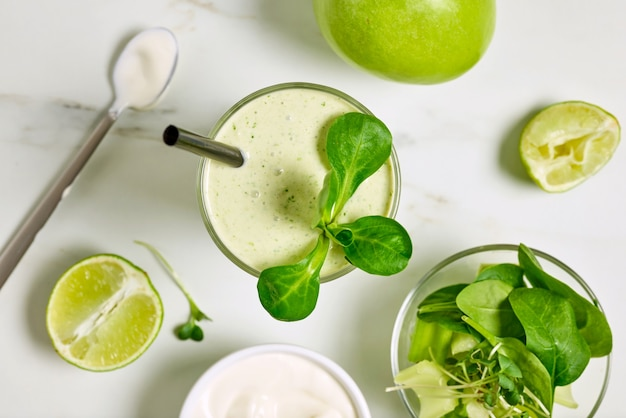 Glas grüner smoothie und zutaten auf küchentisch, ansicht von oben
