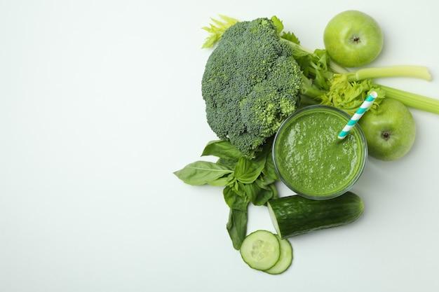 Glas grüner smoothie und zutaten auf weißem hintergrund, platz für text
