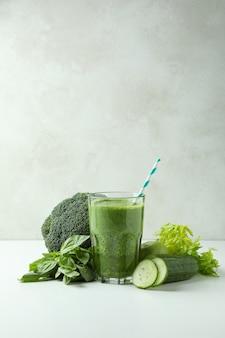 Glas grüner smoothie und zutaten auf weißem tisch