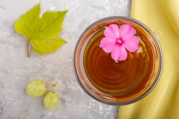 Glas grüner traubensaft mit grünem gewebe und rosa blume. ansicht von oben