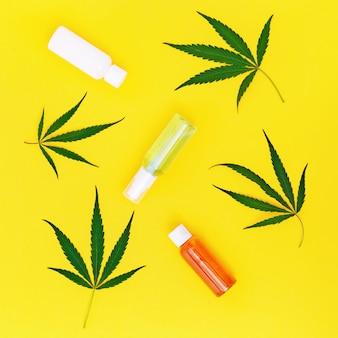 Glas hanfcreme und grüne blätter von cannabis.