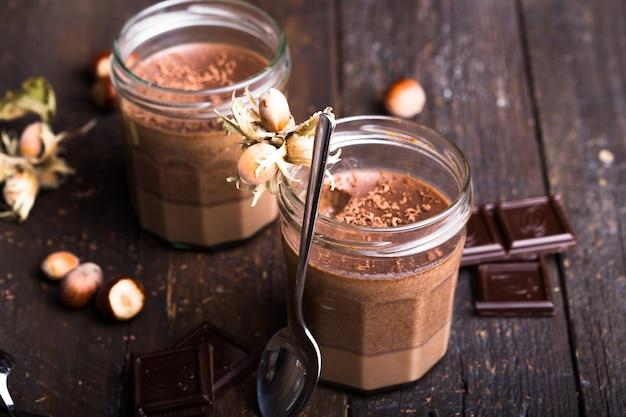 Glas hausgemachten joghurt mit schokoladenmousse und praline und löffel