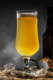 Glas hausgemachtes bier auf einem holztisch. glas craft beer auf dunklem hintergrund.