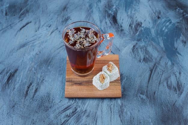 Glas heißen schwarzen tee mit süßen köstlichkeiten auf blauer oberfläche.