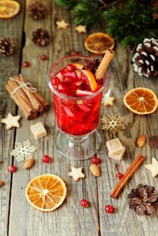 Glas heißer glühwein für das neue jahr mit zutaten zum kochen, nüssen und weihnachtsdekorationen