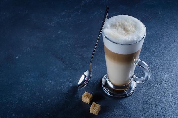 Glas heißer latte-macchiato-kaffee auf blauem konkretem steintabellenhintergrund. morgengetränk