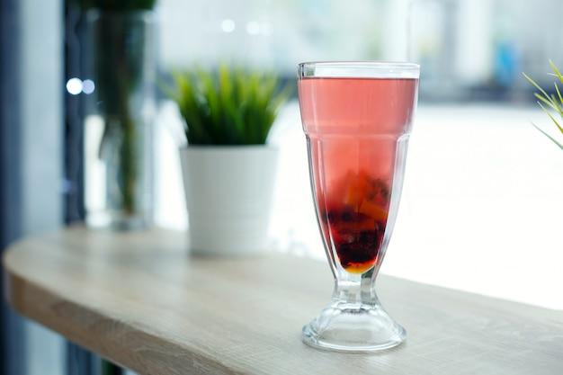 Glas heißer vitamintee auf holztisch. winter heiße saisonale getränke
