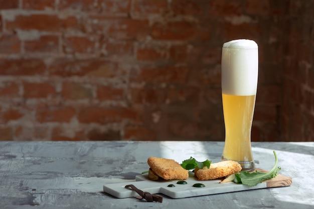 Glas helles bier auf dem steintisch und der backsteinmauer.