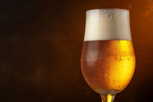 Glas helles bier auf einem holztisch.