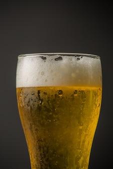 Glas helles bier auf schwarzem hintergrund