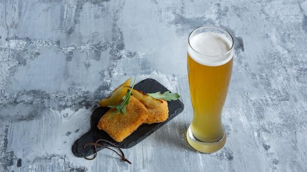 Glas helles bier auf weißer steinoberfläche