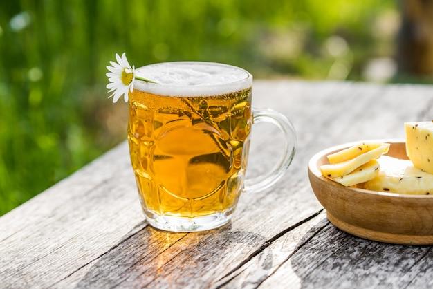 Glas helles bier mit käse und kamille