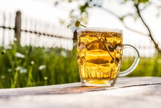 Glas helles bier und kamille auf natur