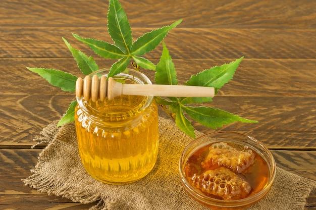 Glas honig, holzlöffel und hanfblätter nahaufnahme auf holzhintergrund. gesunde cbd-produkte. süßer nachtisch. alternative medizin.