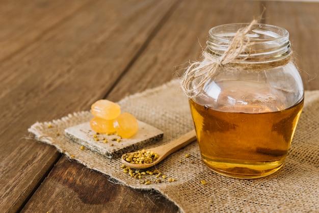 Glas honig mit bienenblütenstaubkernen und -süßigkeiten auf sackstoff