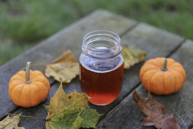 Glas honig neben zwei kürbissen