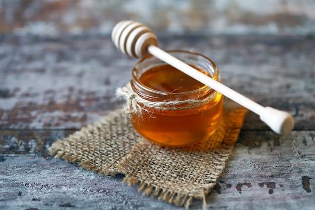 Glas honig und einen löffel für honig.