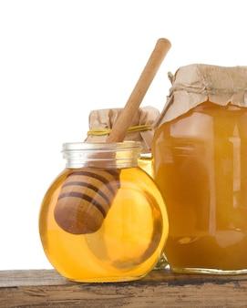 Glas honig und stick isoliert auf weiß