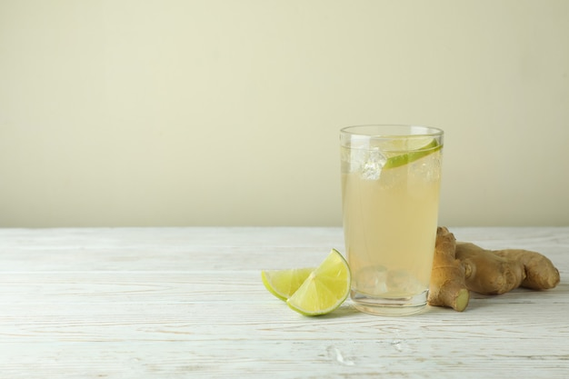 Glas ingwerbier und zutaten auf weißem holztisch